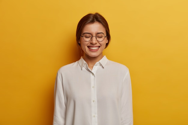 Freundliche positive europäische studentin sieht mit freudigem ausdruck aus, schließt die augen und grinst in die kamera, trägt eine runde brille und ein weißes hemd