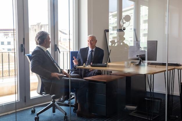 Freundliche reife geschäftspartner treffen sich im büro, sitzen am arbeitsplatz mit laptop und sprechen. blick durch die glaswand. geschäftsporträt-konzept