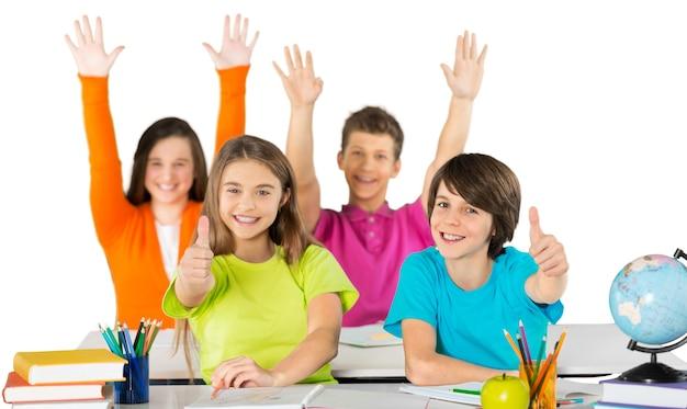 Freundliche schulkinder in der schule, die das thema studieren, daumen nach oben gestikulieren isoliert auf weiß