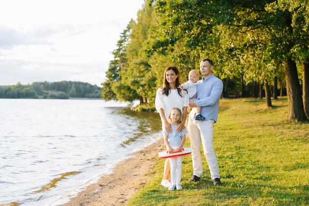 Freundliche stilvolle schöne familie mit zwei kindern stehen am ufer des sees. das mädchen hält ein boot. das konzept von familienurlaub und ferien. kopieren sie platz