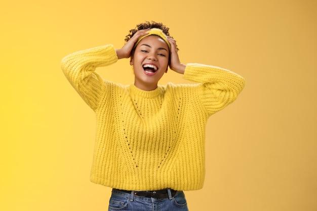 Freundliche, unbeschwerte, fröhliche, lächelnde weiße zähne afroamerikanische frau, die spaß am perfekten tag-offenen touch-kopf hat, sorglos kichernd aussehende kamera amüsiert scherzend bleiben positiv, gelber hintergrund.