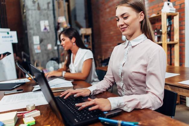Freundliche weibliche büroangestellte, die formelle arbeitskleidung tragen und auf der laptop-tastatur arbeiten.