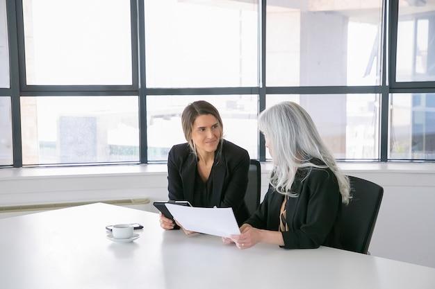 Freundliche weibliche fachleute diskutieren und analysieren berichte. geschäftsfrauen sitzen zusammen, betrachten dokumente, verwenden tablette und sprechen. kommunikationskonzept