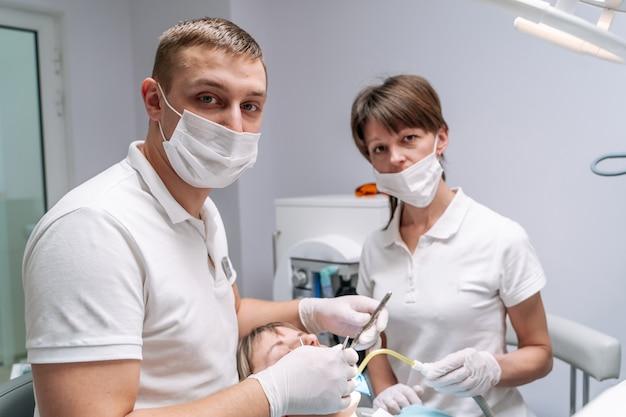 Freundliche zahnärzte mit patientin. regelmäßiger besuch in zahnarztpraxen. moderne stomatologie.