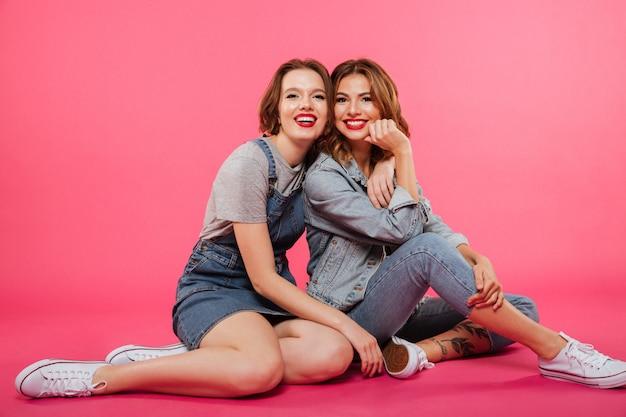Freundliche zwei freundinnen, die auf fußboden sitzen