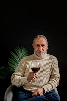 Freundlicher älterer mann mit einem glas wein
