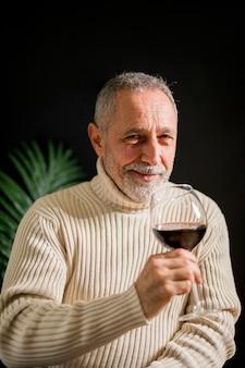 Freundlicher älterer mann mit glas wein
