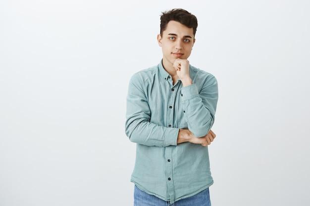 Freundlicher attraktiver europäischer männlicher student im türkisfarbenen hemd
