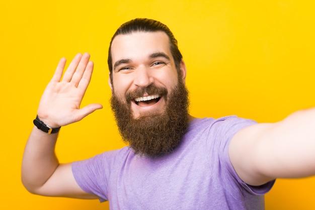 Freundlicher bärtiger mann sagt hallo, während er ein selfie macht.