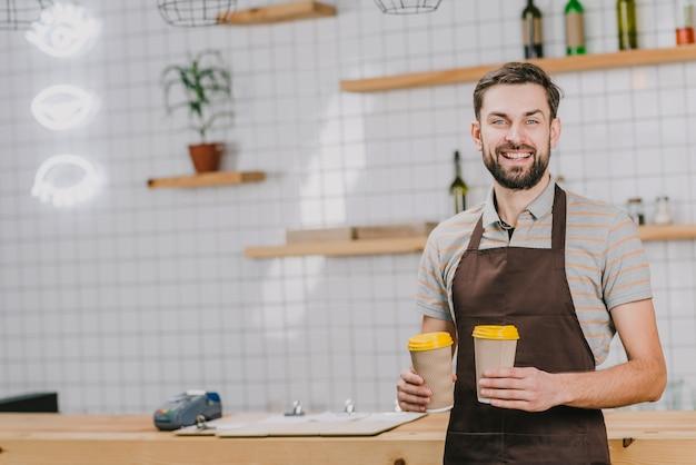 Freundlicher barista mit tassen