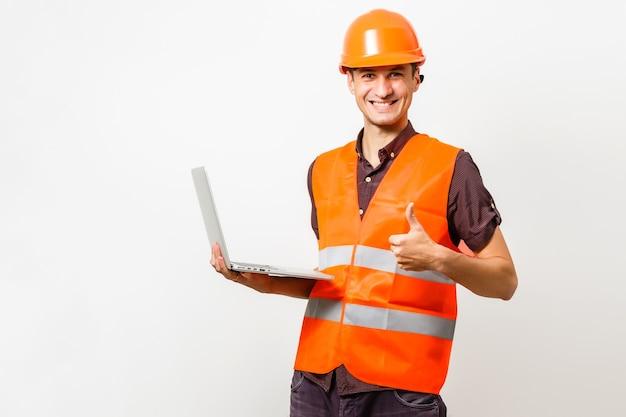 Freundlicher bauarbeiter, der einen laptop mit schwarzem raum für ihre nachricht hält. getrennt auf weiß.