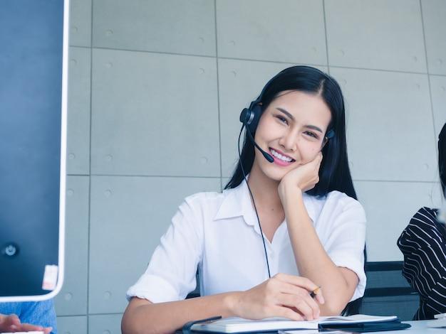 Freundlicher bedienerfrauenagent mit den kopfhörern, die in einem kundenkontaktcenter arbeiten