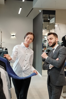 Freundlicher berater eines bekleidungsgeschäfts in bluse, der eine neue kollektion von kleidern demonstriert, während er mit dem kunden im geschäft arbeitet