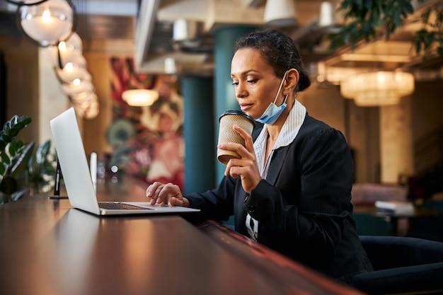 Freundlicher büroangestellter, der einen pappbecher in der hand hält, während er auf den bildschirm des computers starrt