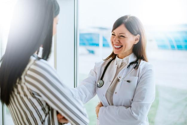 Freundlicher doktor, der mit ihrem patienten spricht