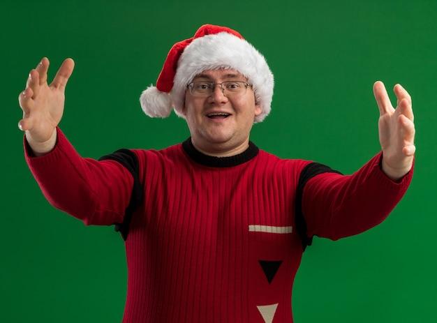 Freundlicher erwachsener mann, der brille und weihnachtsmütze trägt und kamera betrachtet, die willkommensgeste lokalisiert auf grünem hintergrund tut