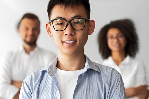 Freundlicher ethnischer kerl in den gläsern, die lächeln und kamera betrachten, während neue rekruten einladen, in der modernen gesellschaft zu arbeiten