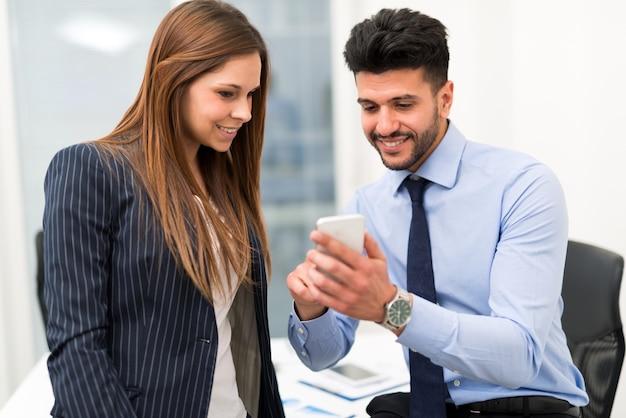 Freundlicher geschäftsmann, der einem weiblichen kollegen im büro den smartphone im büro zeigt