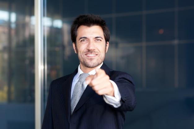 Freundlicher geschäftsmann, der seinen finger auf sie zeigt