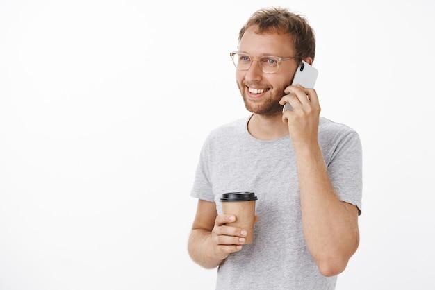 Freundlicher glücklicher kerl, der per telefon spricht und kaffee trinkt