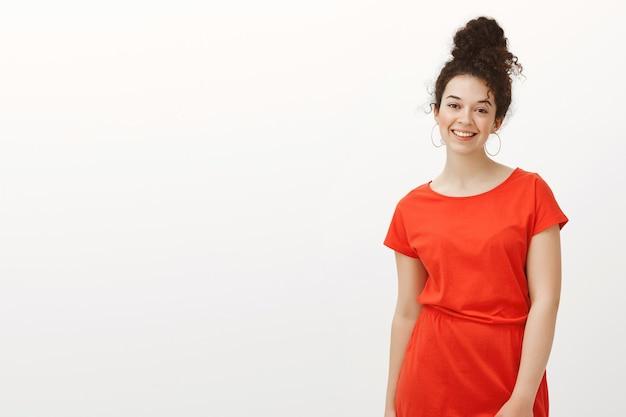 Freundlicher gutaussehender student im roten kleid, fröhlich lächelnd beim posieren