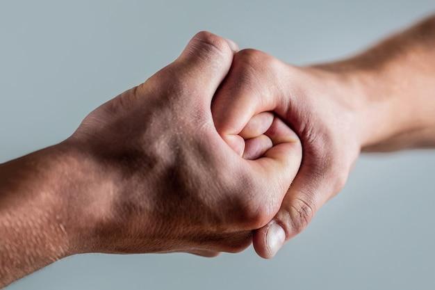 Freundlicher händedruck, begrüßung durch freunde. rettung, helfende hand. männliche hand im händedruck vereint.
