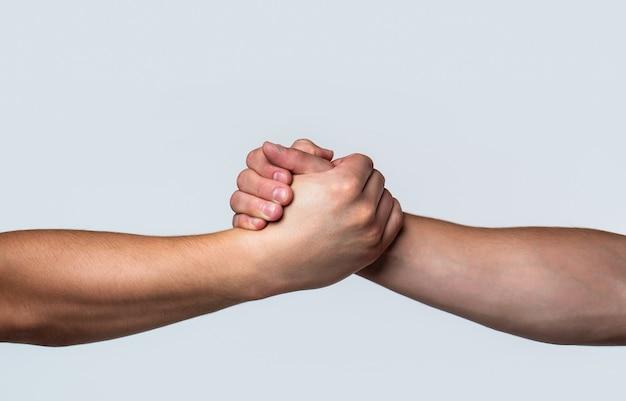 Freundlicher händedruck, begrüßung durch freunde, teamwork, freundschaft. rettung, helfende geste oder hände.