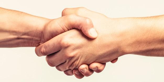 Freundlicher händedruck, freunde grüßen, teamwork, freundschaft. nahaufnahme. rettung, helfende geste oder hände. starker halt. zwei hände, helfende hand eines freundes.