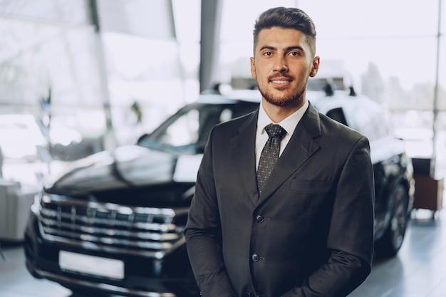 Freundlicher hübscher autoverkäufermann, der im autosalon steht