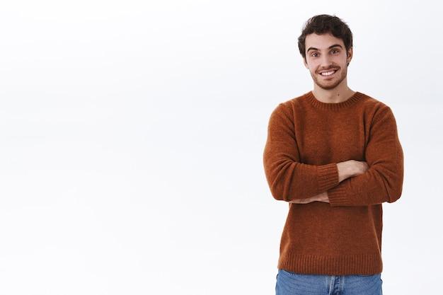 Freundlicher hübscher junger bärtiger mann, der mit verschränkten armen posiert
