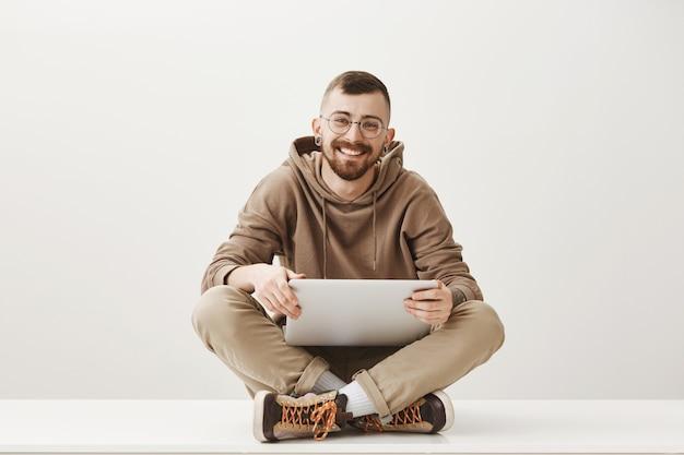 Freundlicher hübscher junger mann sitzt mit laptop und lächelt