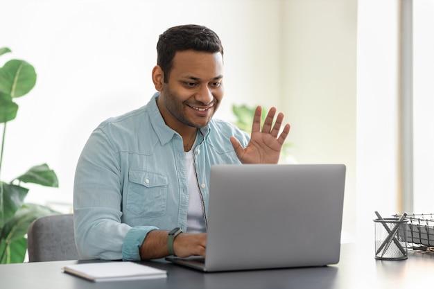 Freundlicher junger indischer mann, der laptop für die videokommunikation mit mitarbeitern verwendet. männlicher freiberufler in freizeitkleidung winkt mit der hand vor der webcam, die online-teilnehmer begrüßt