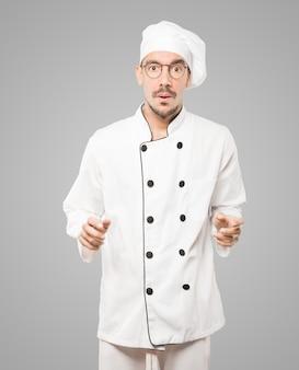 Freundlicher junger koch, der eine geste der bewunderung tut