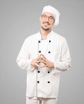 Freundlicher junger koch, der eine geste des vertrauens tut