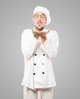 Freundlicher junger koch, der eine geste macht, einen kuss mit seiner hand zu senden