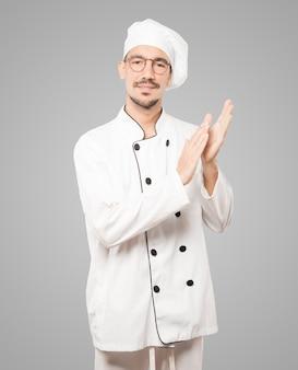 Freundlicher junger koch, der geste applaudiert