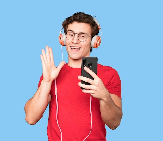 Freundlicher junger mann, der ein selfie mit seinem smartphone nimmt