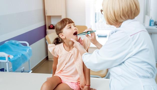 Freundlicher kinderarzt mit geduldigem kind in der klinik