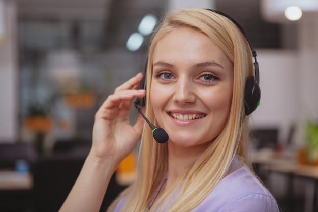 Freundlicher kundendienstmitarbeiter mit dem kopfhörer, der im call-center arbeitet