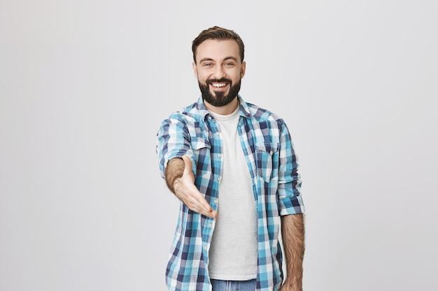 Freundlicher lächelnder kerl strecken hand für handschlag, grußgeste aus