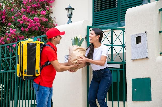 Freundlicher lebensmittelkurier mit isothermem rucksack, der dem kunden ein paket vom lebensmittelgeschäft gibt. versand- oder lieferservicekonzept