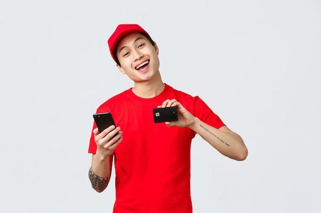Freundlicher lieferbote in rotem uniform-t-shirt und mütze, der smartphone-bildschirm und kreditkarte zeigt, empfiehlt die anwendung zur verfolgung von online-shopping-bestellungen. kurier werben für den spediteurservice