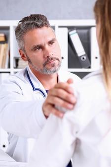 Freundlicher männlicher arzt hält patientenschulter im büro während des empfangs