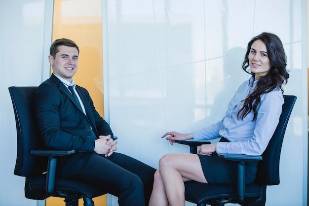 Freundlicher manager sitzt auf stühlen