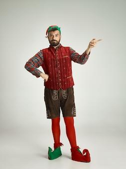 Freundlicher mann gekleidet wie ein lustiger gnom, der auf einem isolierten grau aufwirft