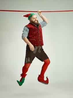 Freundlicher mann gekleidet wie ein lustiger gnom, der auf einem isolierten grau posiert