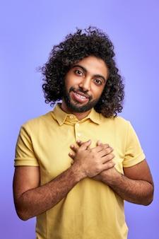 Freundlicher mann sagt danke an der kamera isoliert, arabischer mann im lässigen t-shirt im studio