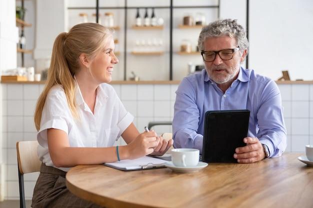 Freundlicher reifer mentor, der freudigen praktikanten projektdetails erklärt