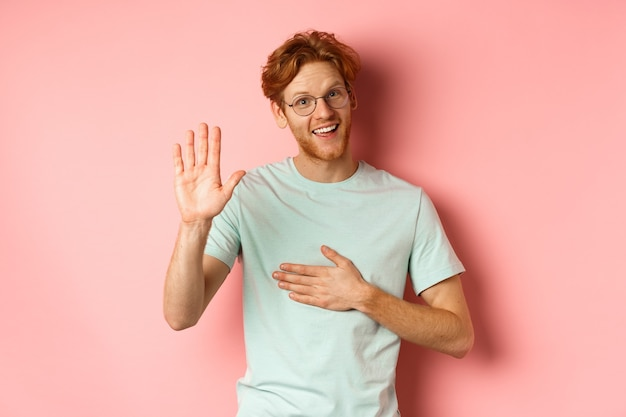 Freundlicher rothaariger mann, der ehrlich ist, hand auf herz und arm hält, die hoch erhoben werden, um zu schwören oder zu versprechen, in die kamera lächelnd, wahrheit über rosa hintergrund sagend.