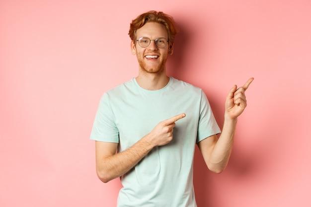 Freundlicher rotschopf mit brille, der auf die obere rechte ecke zeigt, ein werbebanner zeigt und auf c lächelt.